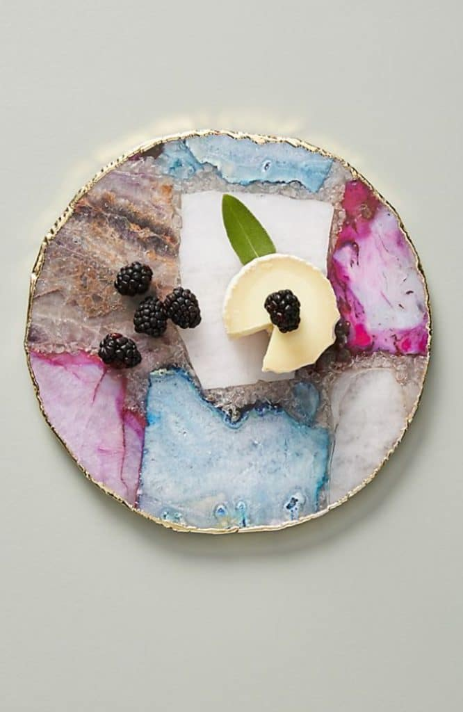 Overhead view of pretty colored agate cheese plate with cheese and berries on it