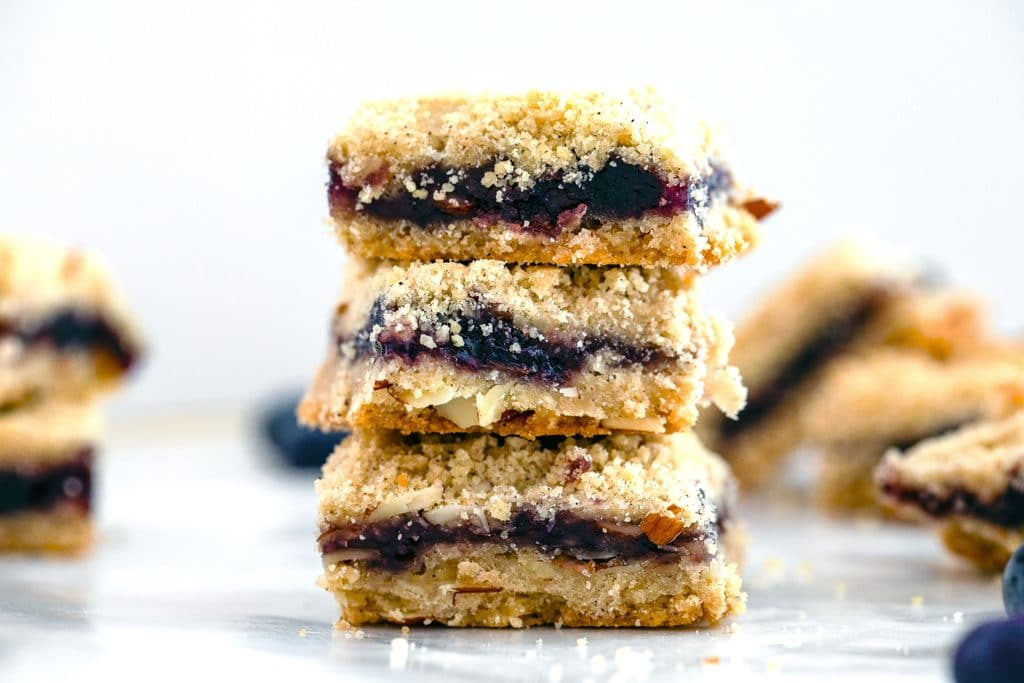 Landscape view of three almond blueberry bars stacked on each other with additional bars in the background
