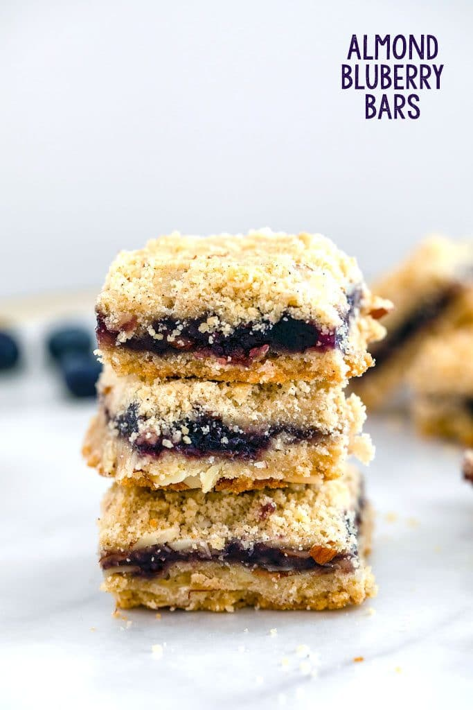 Head-on view of stack of three almond blueberry bars on marble surface with recipe title at top