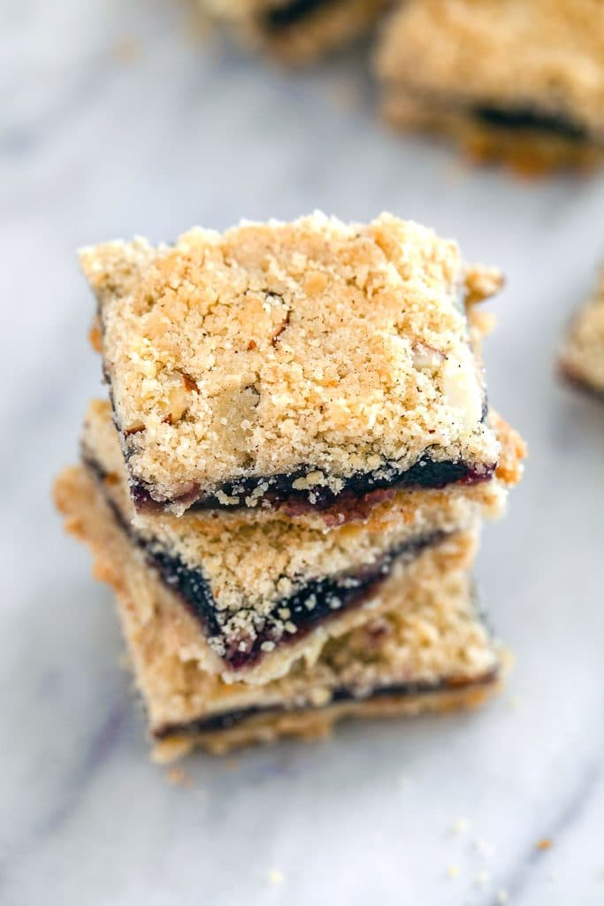 Overhead view of stack of three almond blueberry bars on a marble surface