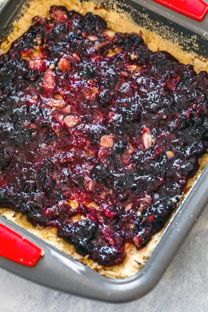 Overhead view of almond dough pressed into the bottom of the pan with blueberry jam spread over the top