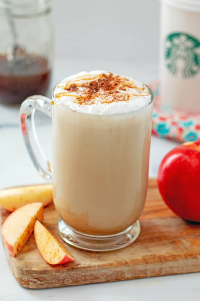 Head-on view of Starbucks Apple Crisp Macchiato with apples all around and Starbucks cup and jar of simple syrup in the background