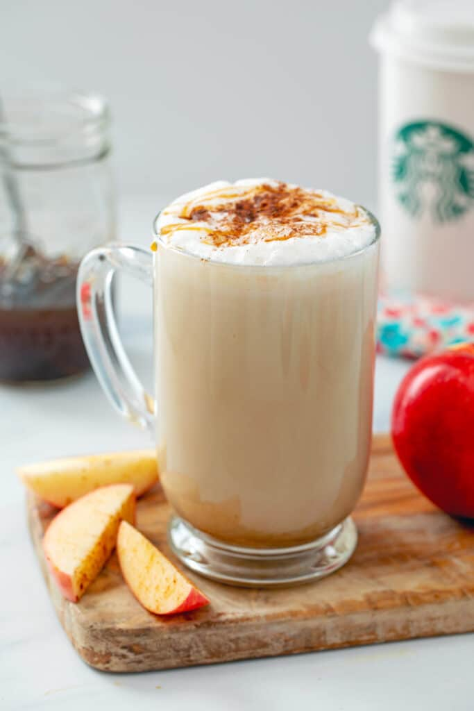 Starbucks copycat Apple Crisp Macchiato in a large mug with apples, apple simple syrup, and Starbucks cup in background