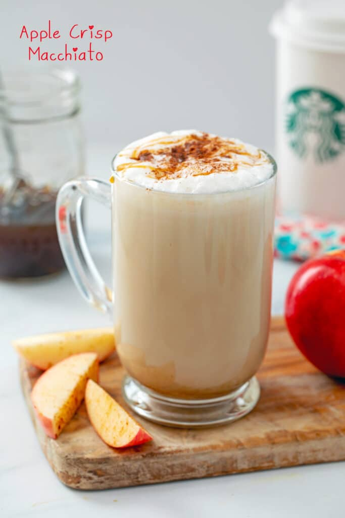Starbucks copycat Apple Crisp Macchiato in a large mug with apples, apple simple syrup, and Starbucks cup in background with recipe title at top