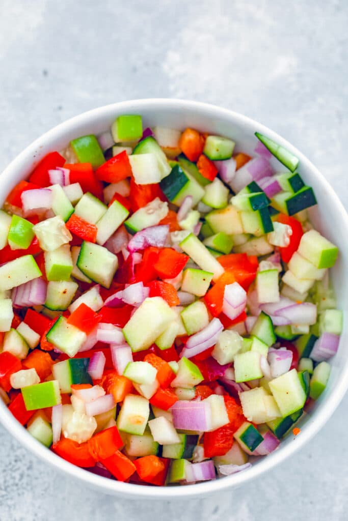 Overhead view of a bowl with apple cucumber salsa with red pepper and red onion