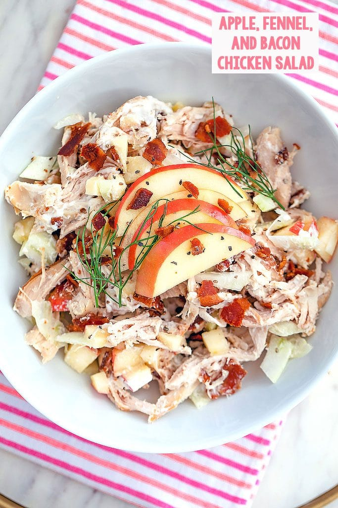 Overhead view of apple, fennel, and bacon chicken salad topped with sliced apples and fennel fronds on a pink and red striped towel with recipe title at the top