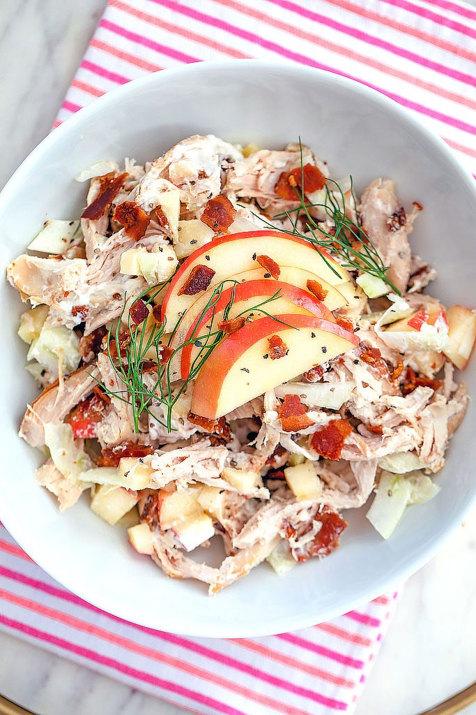 Overhead view of apple, fennel, and bacon chicken salad topped with sliced apples and fennel fronds on a pink and red striped towel