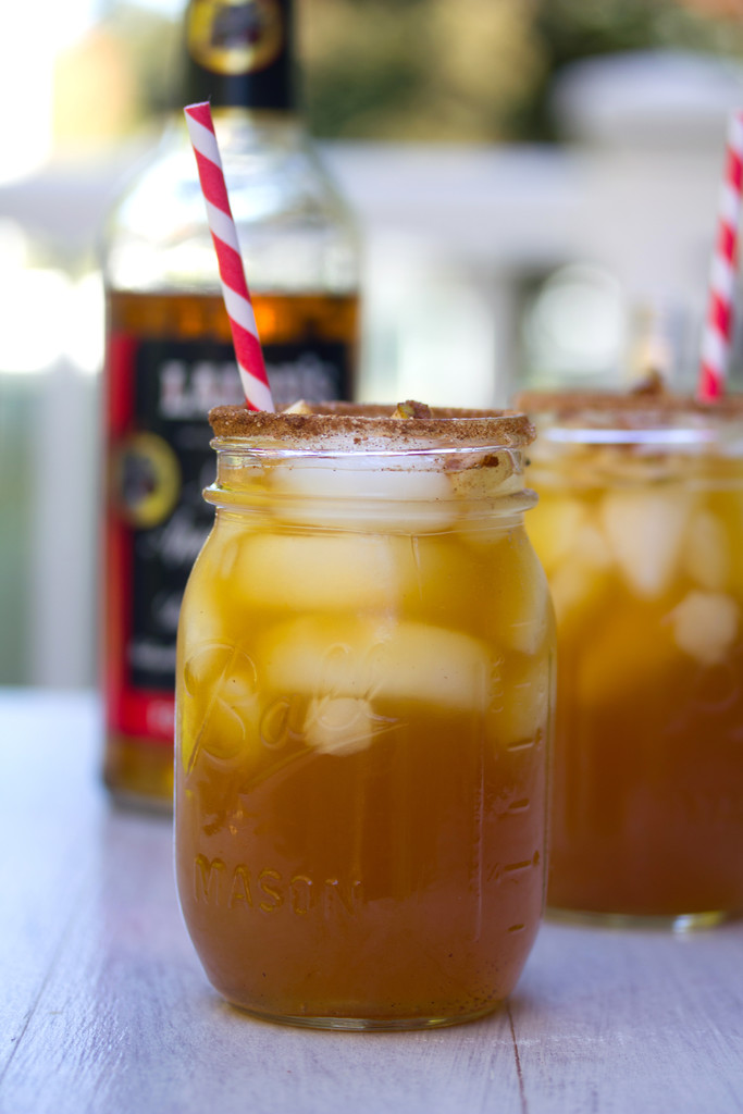 Head-on view of two apple ginger margaritas in mason jars with cinnamon rim, apple garnish, and red and white striped straw with second cocktail and bottle of apple brand in the background