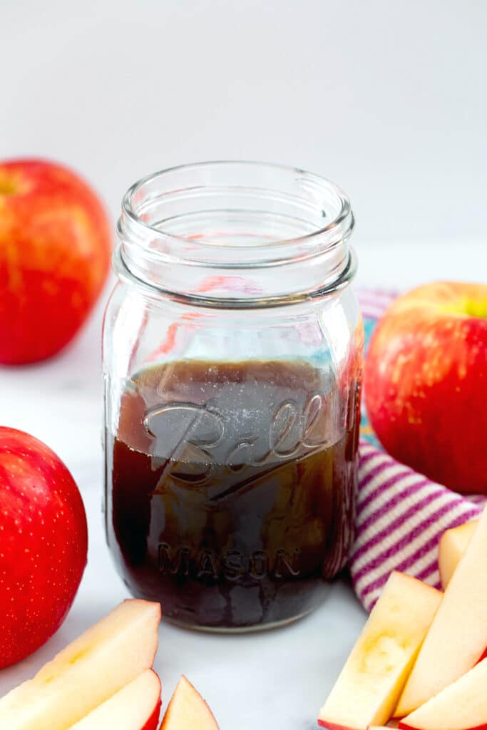 Overhead view of a mason jar of apple simple syrup with sliced apples and whole apples all around