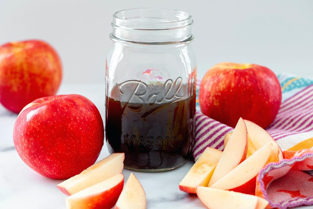 Landscape head-on view of a mason jar of apple simple syrup with apples all around