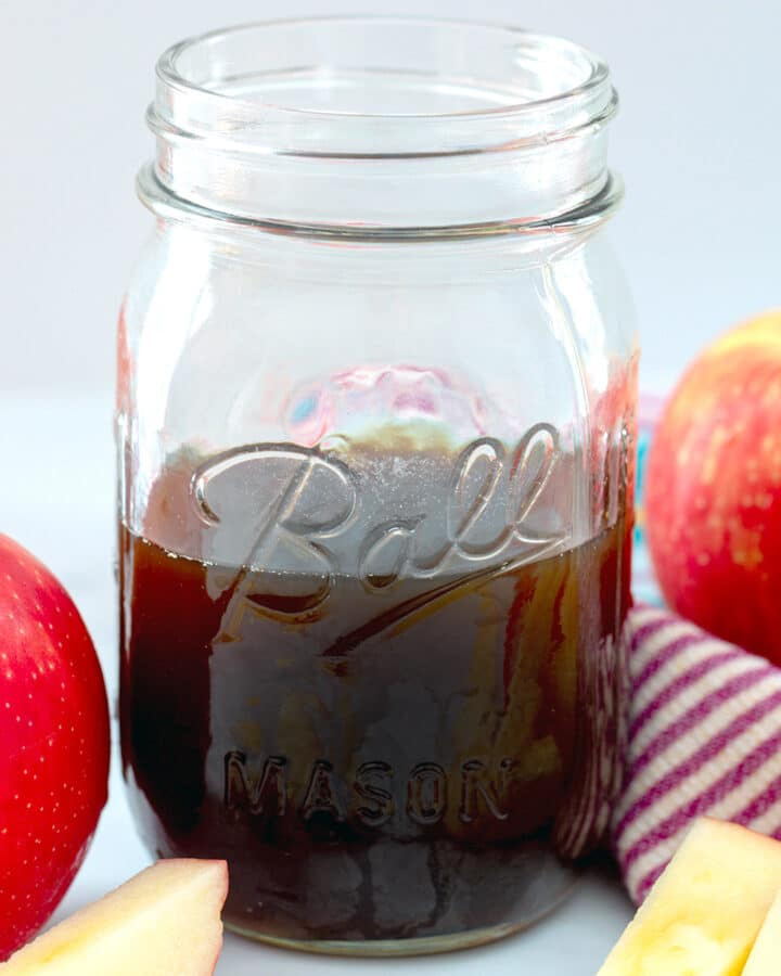 Close-up view of a mason jar of apple simple syrup with apples all around
