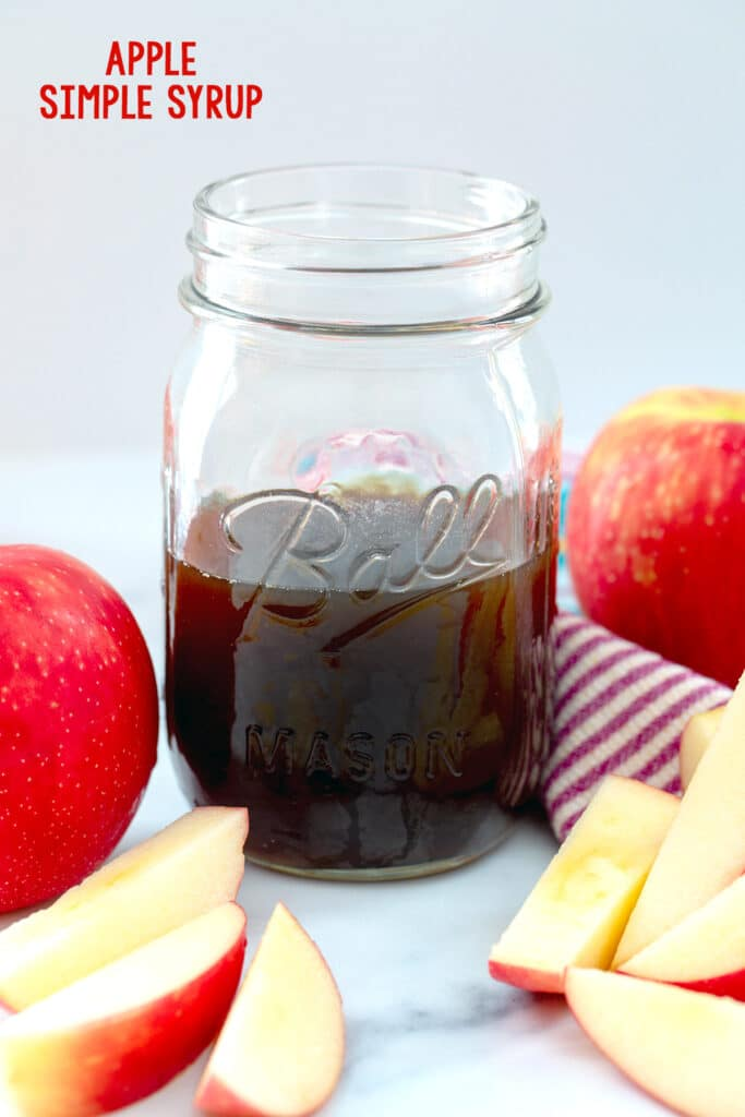 Head-on view of a mason jar of apple simple syrup with whole and sliced apples all around and recipe title at top