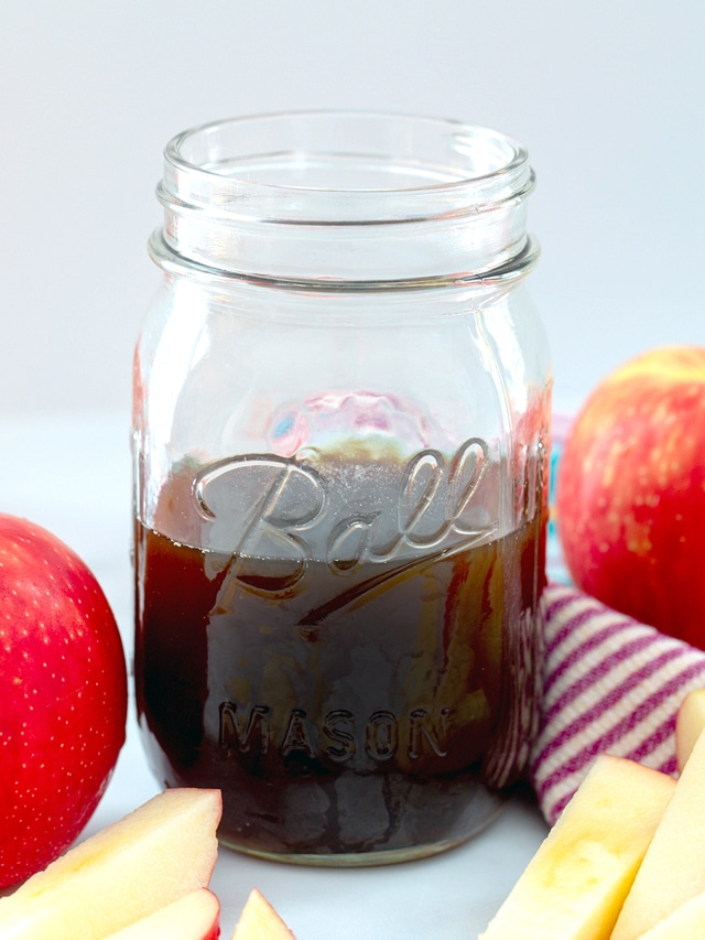 Head-on view of a mason jar of apple simple syrup with apples all around