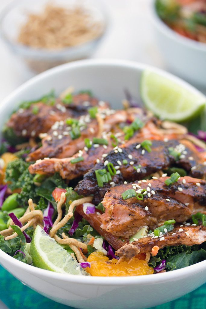Closeup view of miso salmon on top of kale, red cabbage, edamame, and mandarin oranges