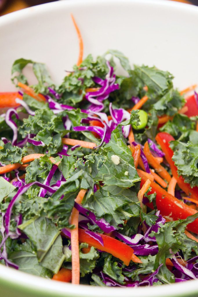 View of salad ingredients in bowl, including kale, red cabbage, grated carrots, red peppers, and edamame