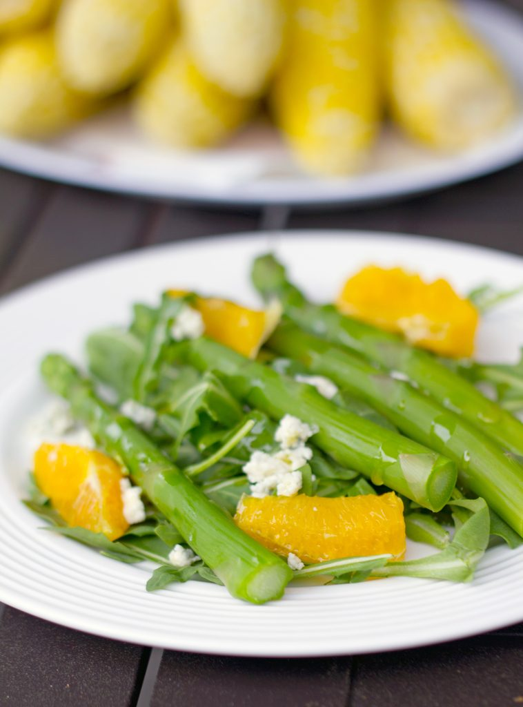 Head-on photo of asparagus salad with orange and gorgonzola with plate of corn in the background