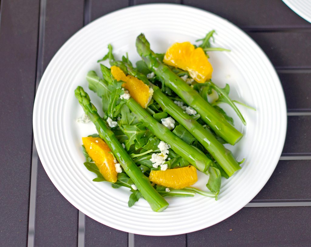 Landscape bird's eye view of asparagus salad with oranges and gorgonzola in a shallow white bowl