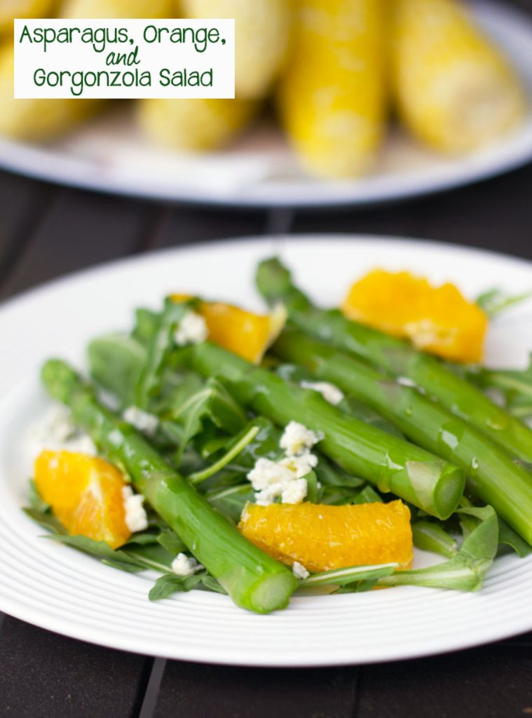 Head-on photo of asparagus salad with orange and gorgonzola with plate of corn in the background and recipe title at top