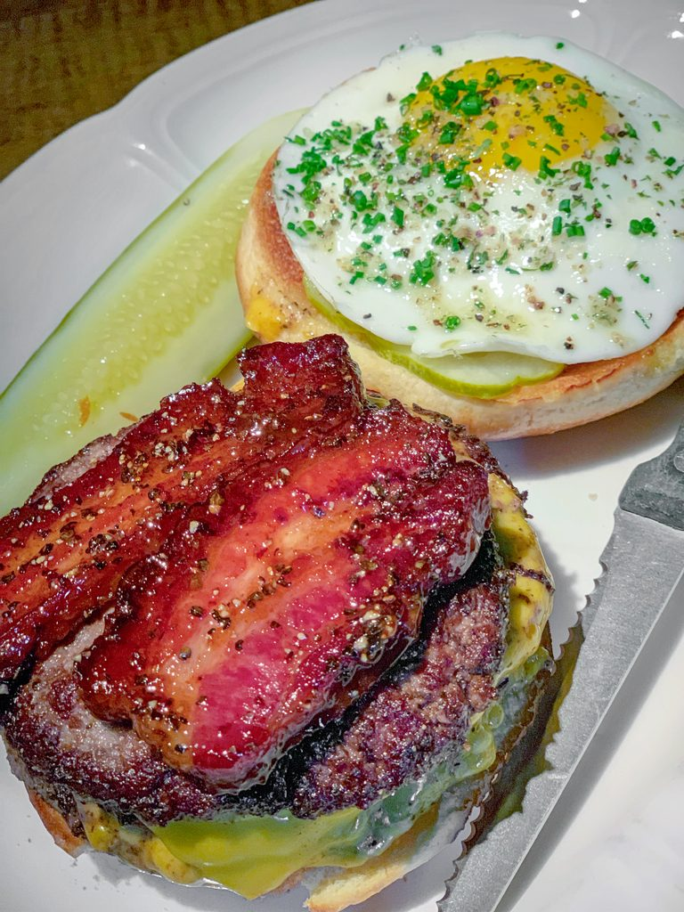 Overhead view of Au Cheval's cheeseburger with thick-cut bacon and sunnyside up egg