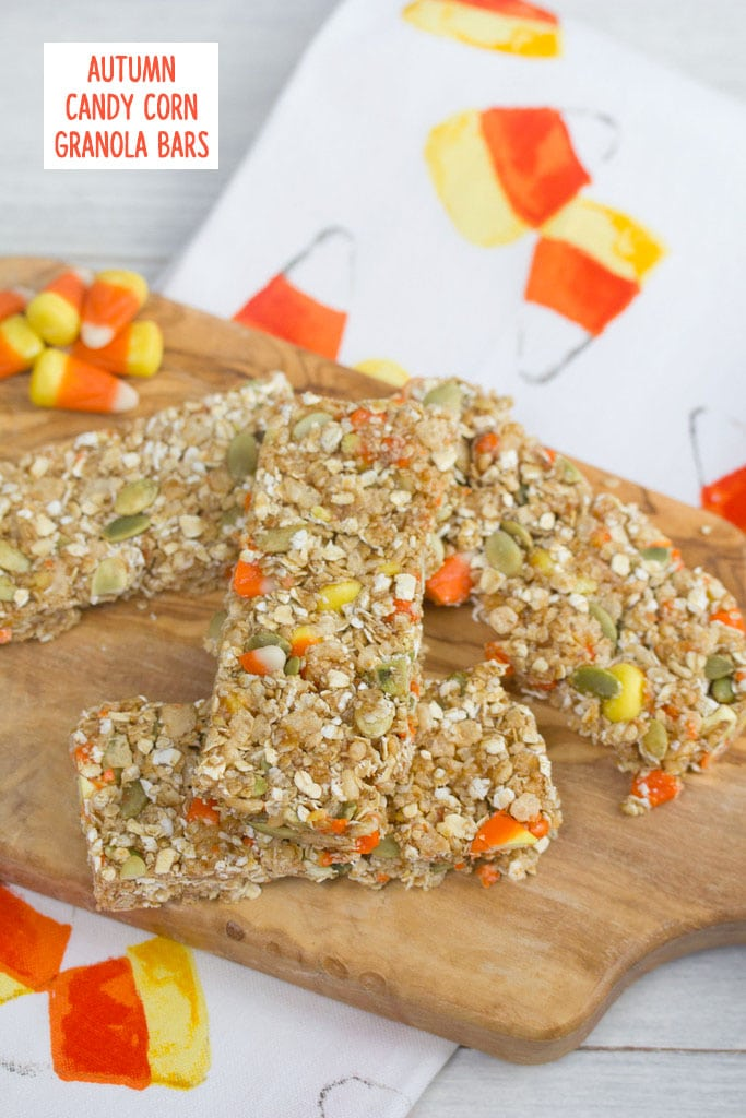 Overhead view of candy corn granola bars on a wooden board with candy corn in background on a candy corn tea towel with recipe title at top
