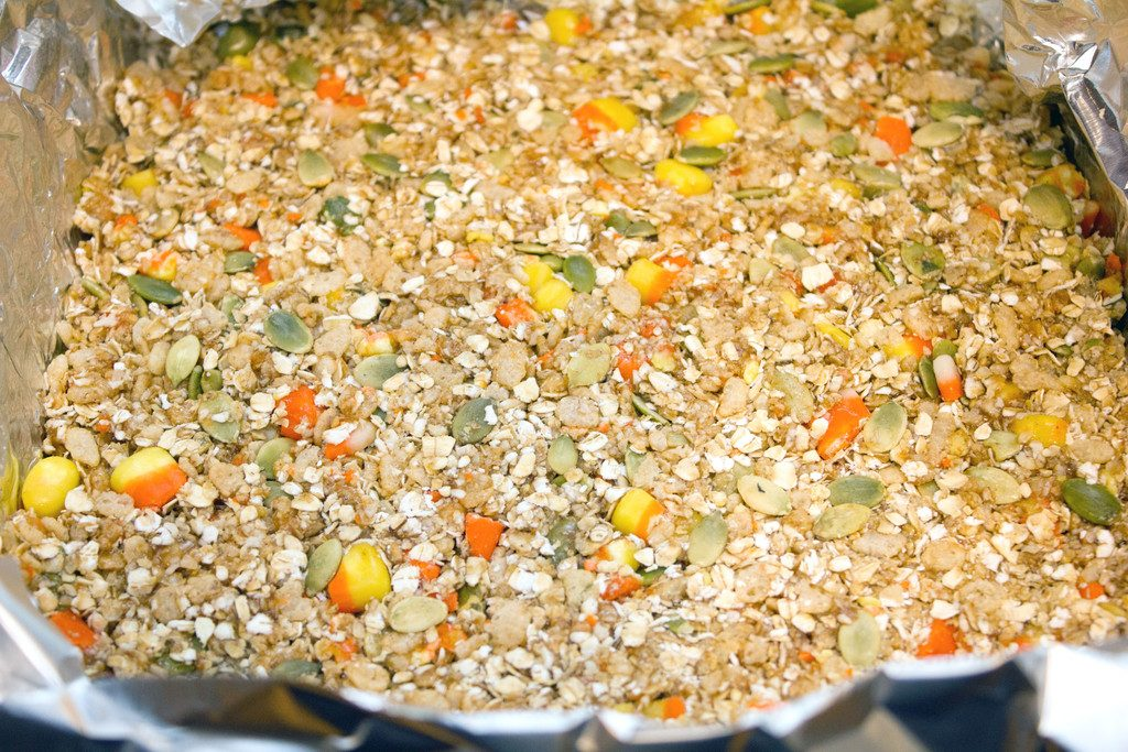 Candy corn granola bar mixture poured into pan and cooling