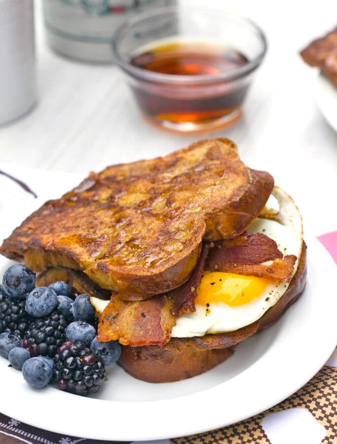 Autumn French Toast Egg Sandwich -- If you can't decide between sweet and savory for breakfast, try this Autumn French Toast Egg Sandwich. This delicious breakfast sandwich is made with fall spiced french toast, crispy bacon, and fried eggs... All slathered in maple syrup! | wearenotmartha.com
