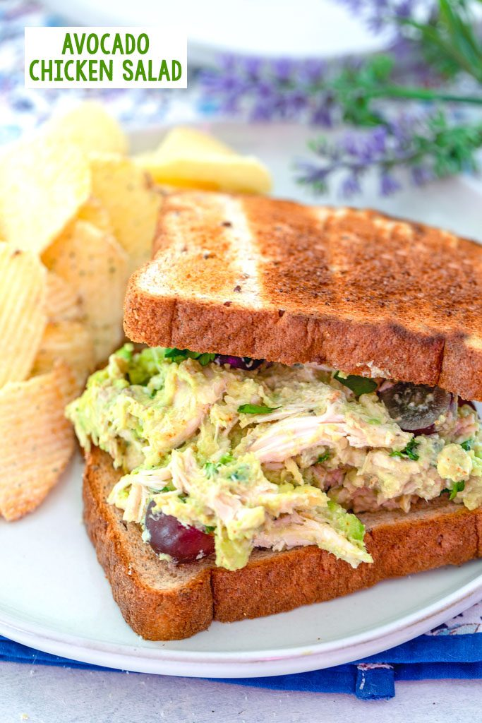 Head-on view of avocado chicken salad sandwich with top slice of bread slightly removed to show chicken salad, with chips on the side and recipe title at top