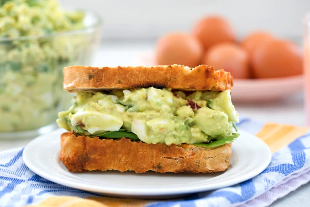 Landscape head-on view of a sandwich filled with avocado egg salad with bowl of egg salad and brown eggs in background
