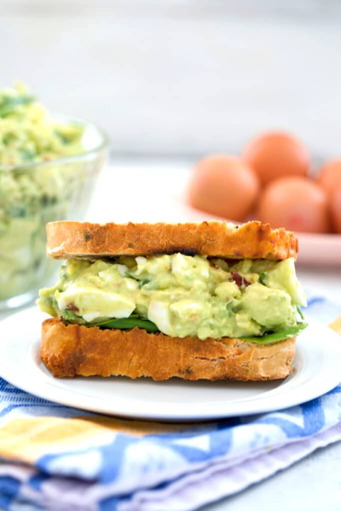Head-on closeup view of an avocado egg salad sandwich with spinach with bowl of egg salad and eggs in the background