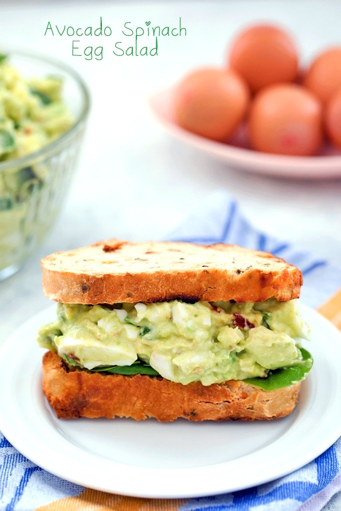 Head-on view of a sandwich packed with avocado egg salad with spinach with bowl of avocado egg salad and eggs in the background and recipe title at top