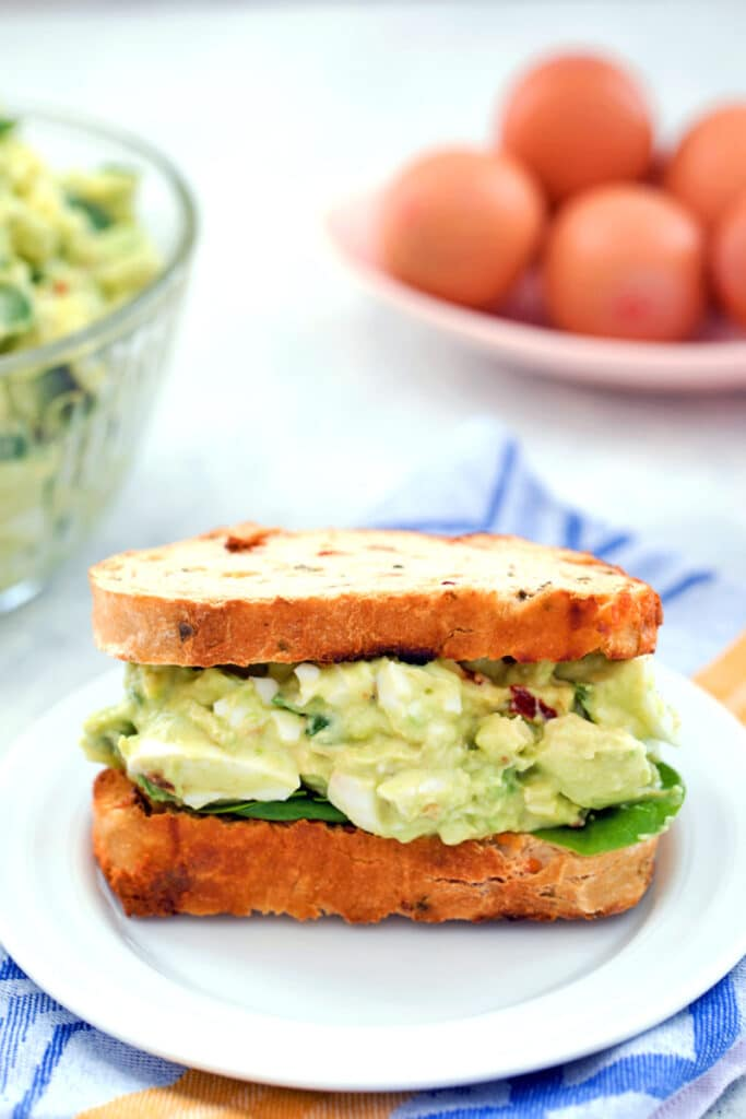 Head-on view of a sandwich packed with avocado egg salad with spinach with bowl of avocado egg salad and eggs in the background