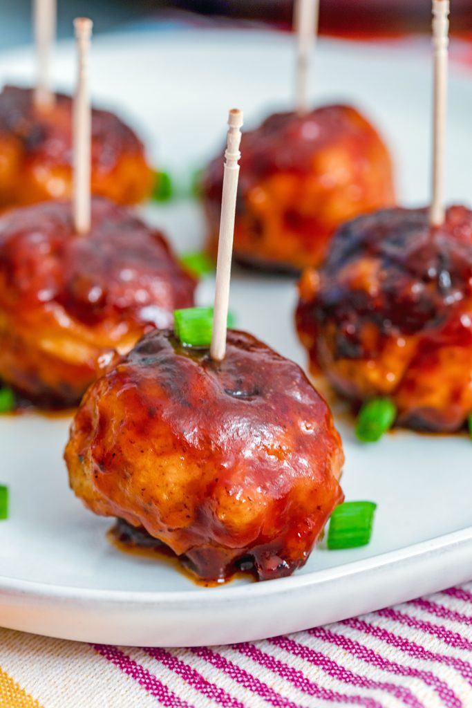 Head-on closeup view of a BBQ Chicken meatball with a toothpick in it with more meatballs in the background and chopped scallions all around