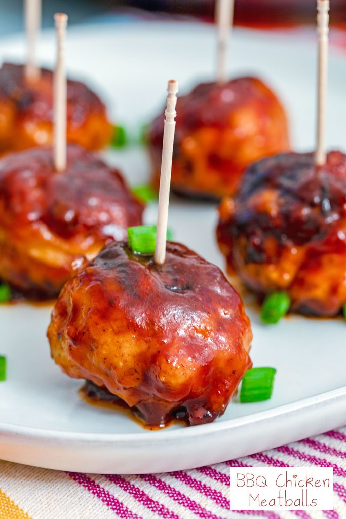 Head-on closeup view of a BBQ Chicken meatball with a toothpick in it with more meatballs in the background, chopped scallions all around, and recipe title at bottom