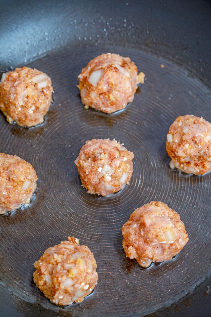 Meatballs formed into golf ball sized balls and cooking in olive oil in skillet