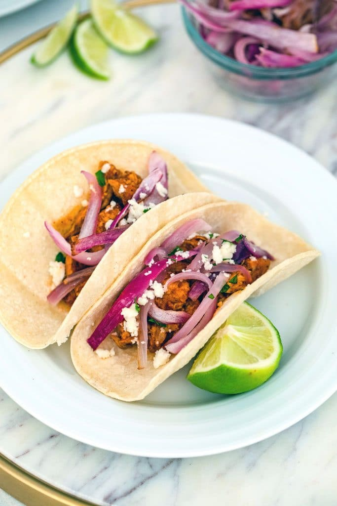 Two BBQ chicken tacos with red onions and white cheese on a white plate with a lime wedge garnish and lime wedges and red onions in the background
