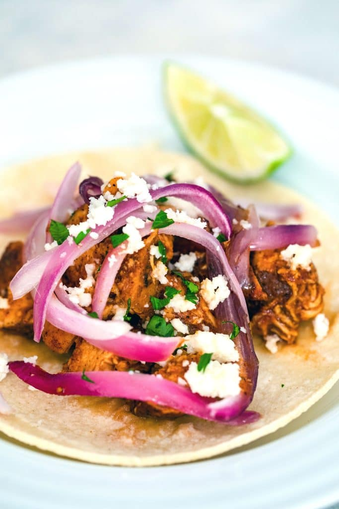 Head-on view of a corn tortilla on a white plate and topped with BBQ chicken, red onions, white cheese, and cilantro with a lime wedge in the background