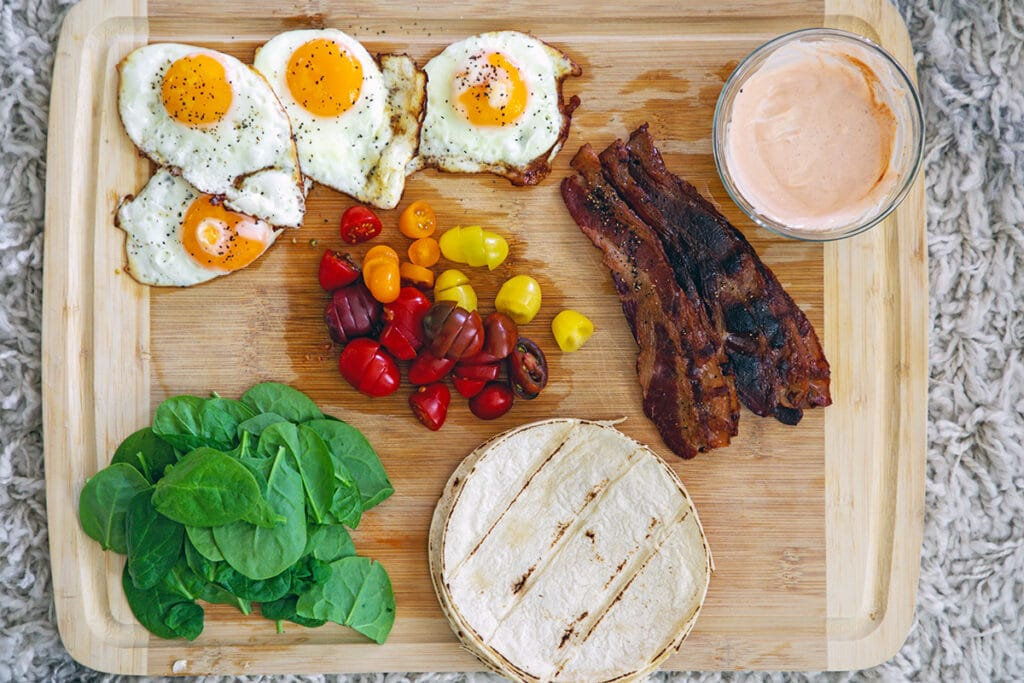 Overhead view of a wooden cutting board with fried eggs, sliced tomatoes, crispy bacon, baby spinach, grilled tortillas, and bowl of sriracha aioli