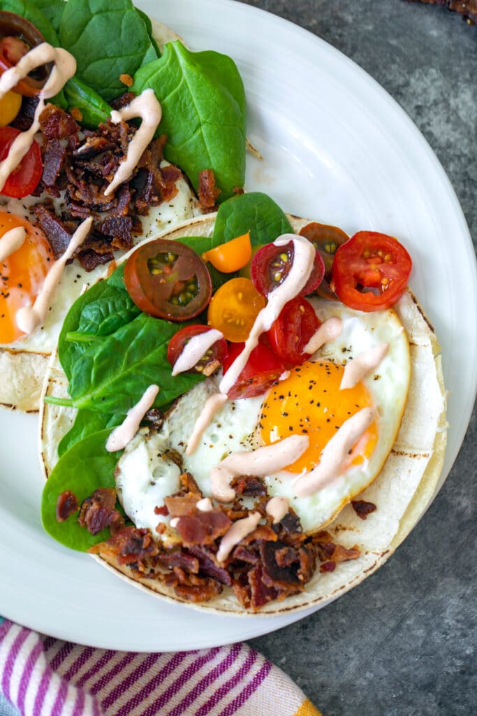 Overhead closeup view of a BLT breakfast taco with fried egg, crumbled bacon, sliced tomatoes, baby spinach, and a sriracha aioli drizzle