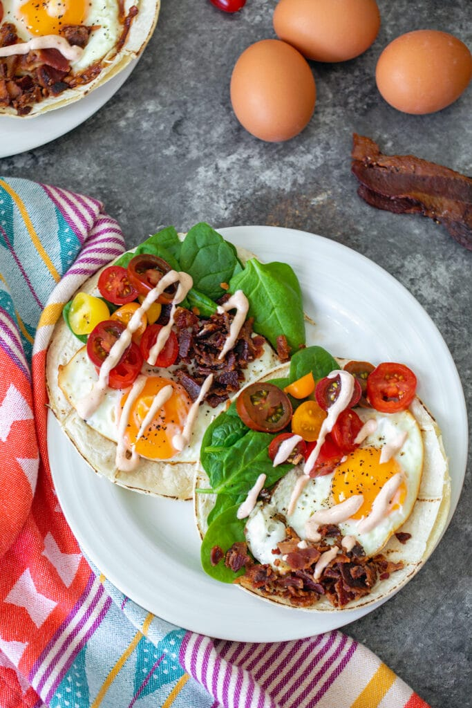 Bird's eye view of two BLT breakfast tacos with fried eggs, bacon, tomatoes, spinach, and sriracha aioli with eggs and bacon and second plate in the background