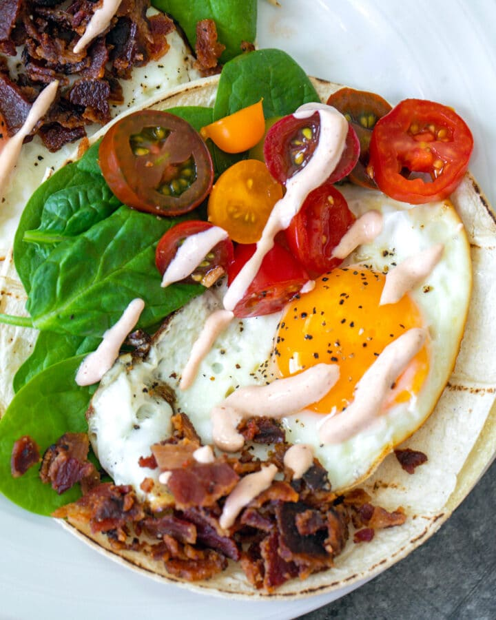 Overhead closeup view of a BLT breakfast taco with fried egg, crumbled bacon, baby spinach, tomatoes, and sriracha aioli drizzle