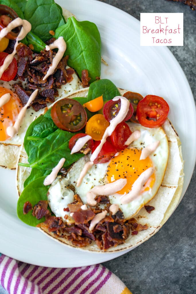 Overhead closeup view of a BLT breakfast taco with fried egg, crumbled bacon, sliced tomatoes, baby spinach, and a sriracha drizzle with recipe title at the top