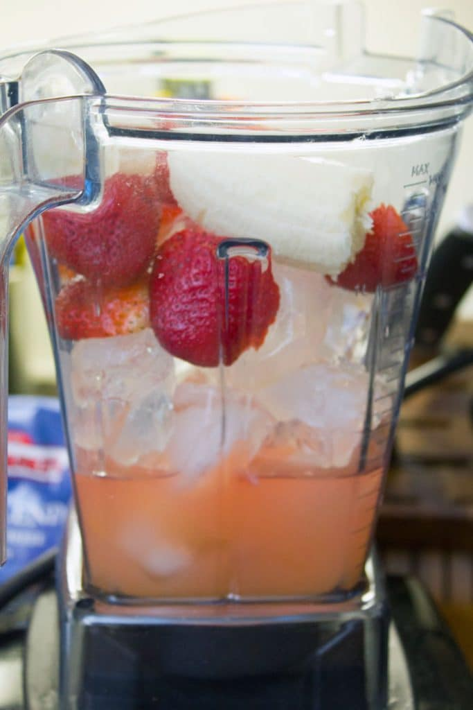 Strawberries, banana, ice, and Bacardi in a blender for making strawberry banana daiquiris