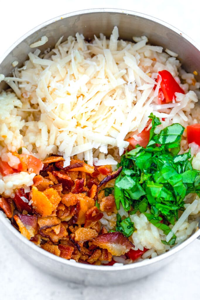 Overhead view of risotto in saucepan topped with grated parmesan, chopped bacon, chopped basil, and chopped tomatoes