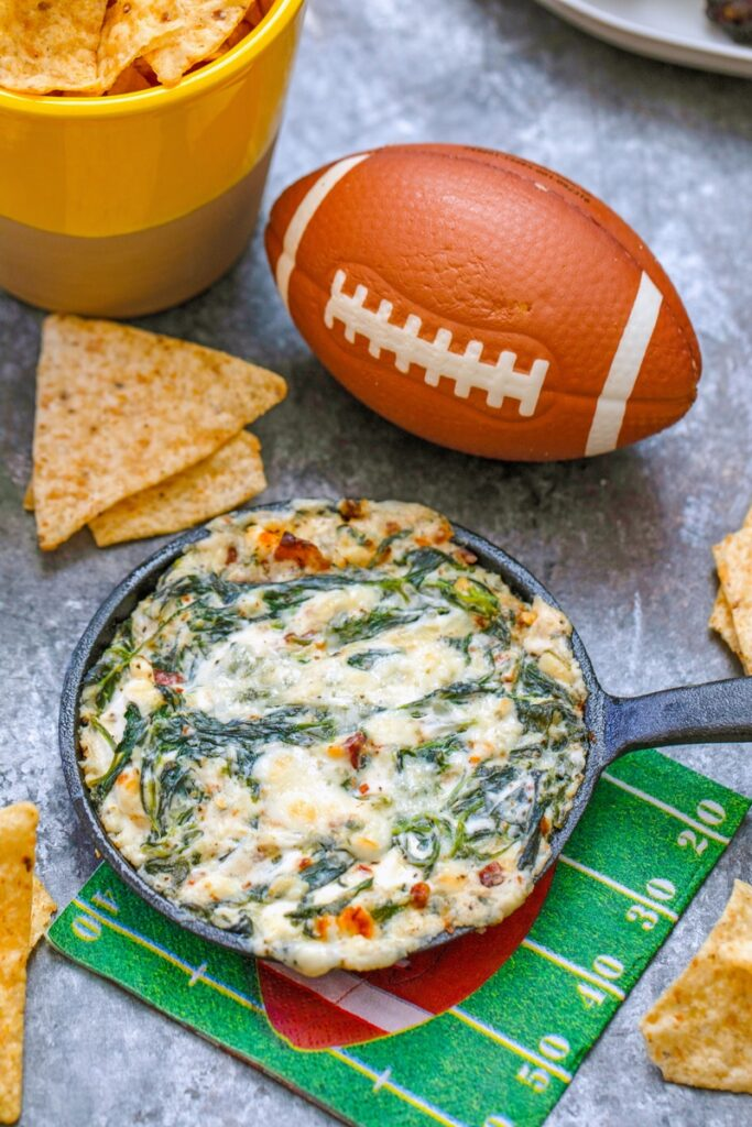 Closeup of bacon blue cheese spinach dip in mini cast iron skillet with tortilla chips and football in background