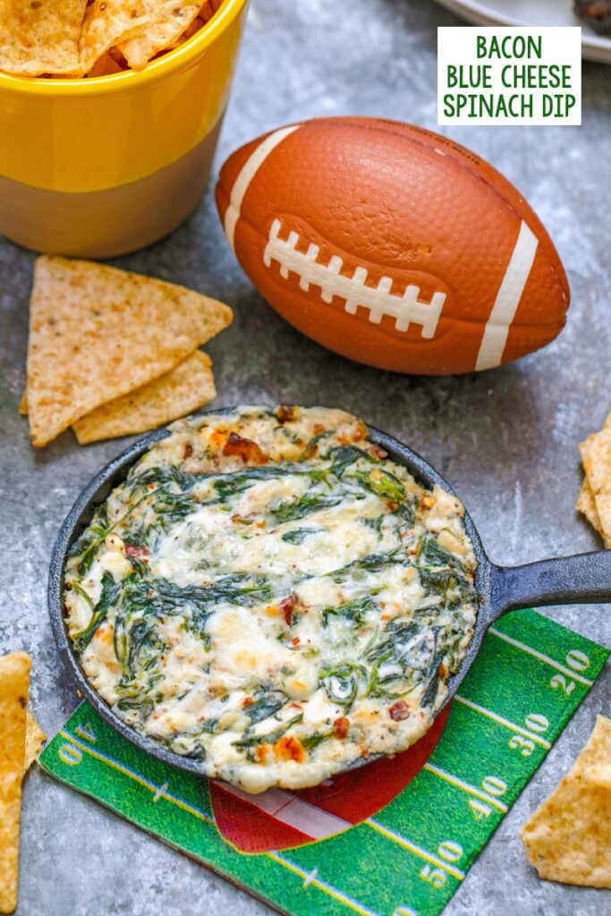 Closeup of bacon blue cheese spinach dip in mini cast iron skillet with tortilla chips and football in background with recipe title at top