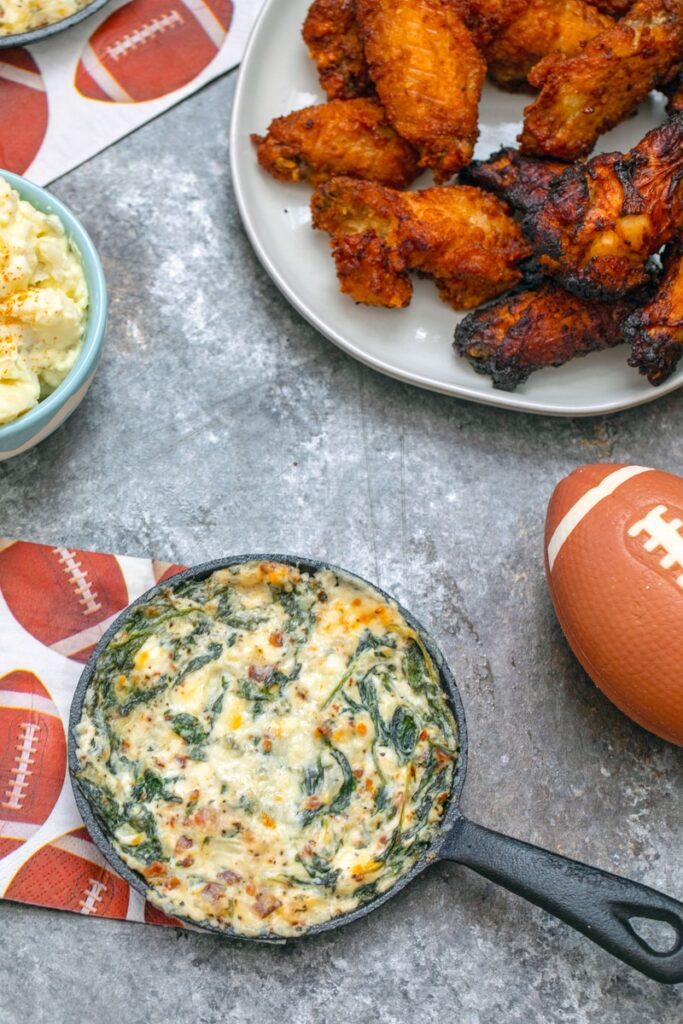 Overhead view of bacon blue cheese spinach dip with chicken wings in background, mini football, and football napkin