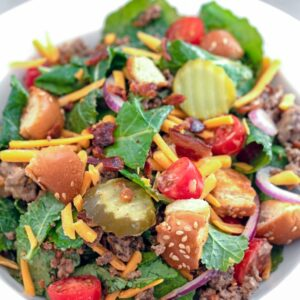 Overhead close-up view of bacon cheeseburger kale salad including baby kale, ground beef, shredded cheddar, dill pickle rounds, chopped tomatoes, red onion, crumbled bacon, and hamburger bun croutons in a white bowl with recipe title at top