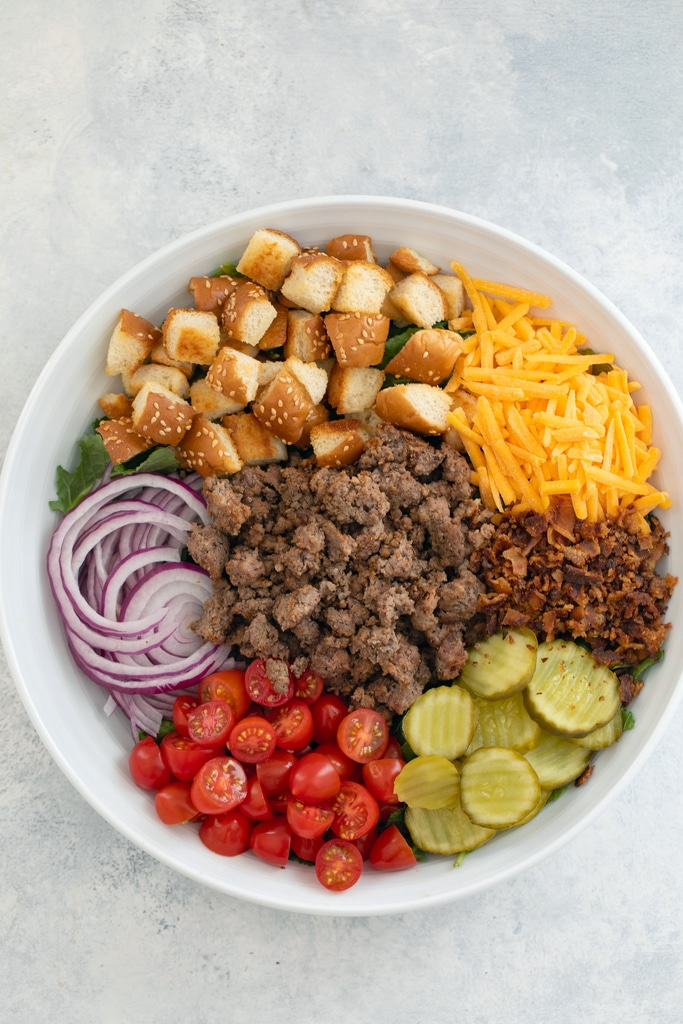 Overhead view of salad ingredients arranged in white serving bowl before tossing, including bed of baby kale with sliced red onion, chopped tomatoes, dill pickle rounds, crumbled bacon, shredded cheddar, hamburger bun croutons, and ground beef