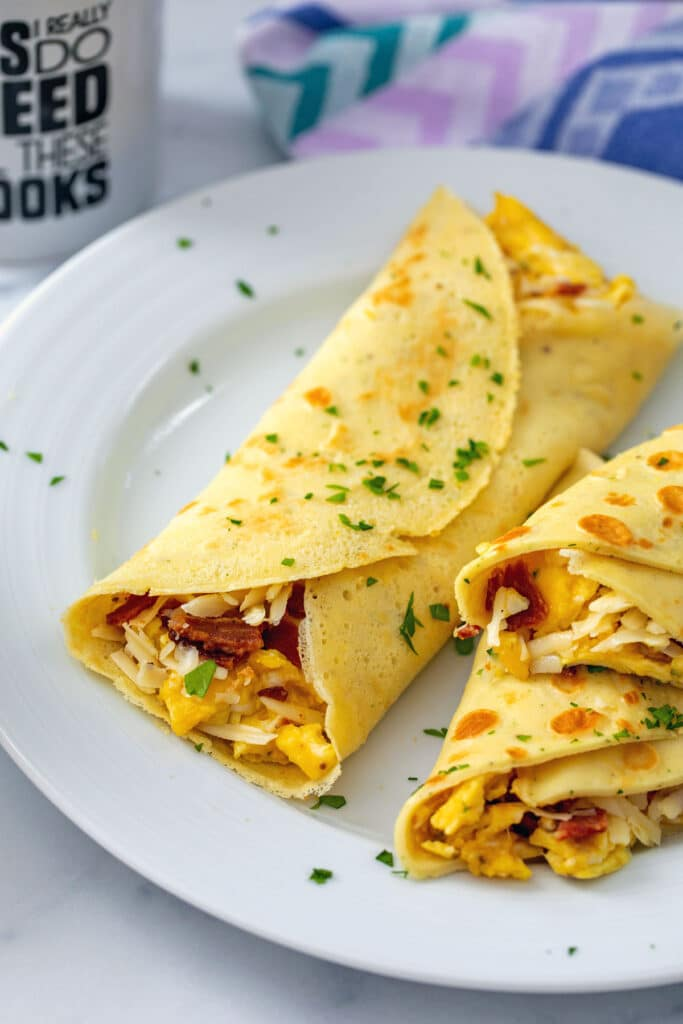 Overhead view of multiple bacon, egg, and cheese crepes on a white plate with parsley sprinkled over the top