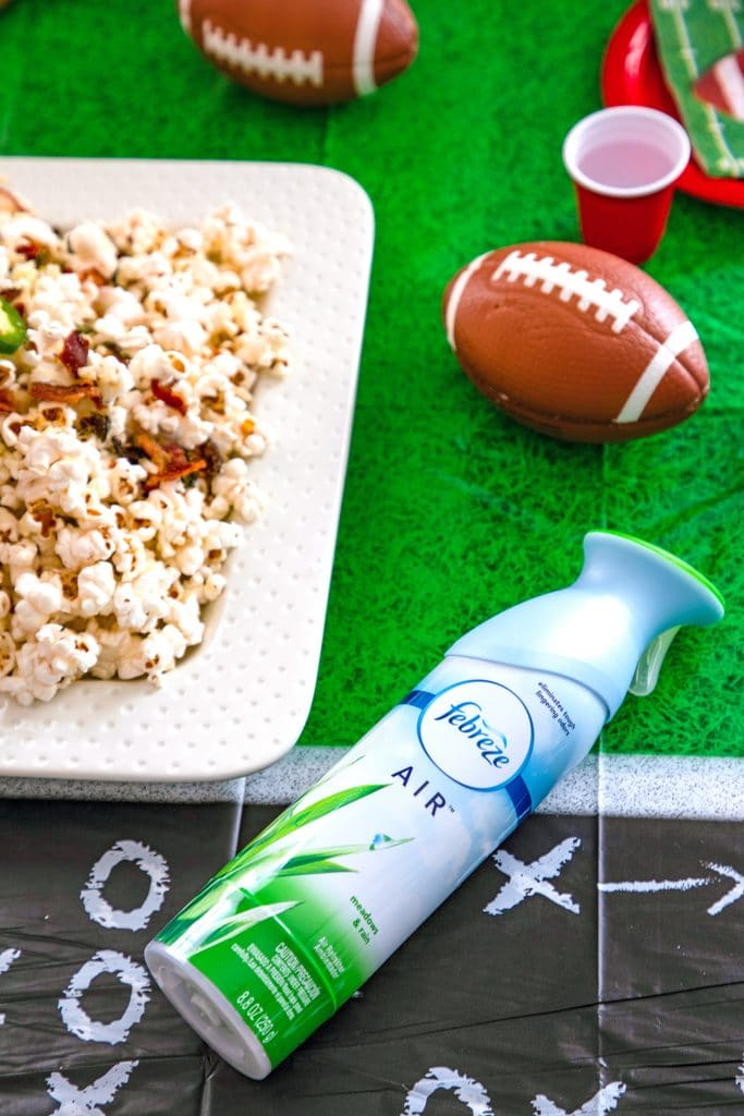 Overhead view of Febreze AIR, platter of jalapeño cheddar popcorn, mini footballs, and cups on a football field tablecloth